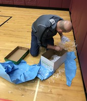Mr. Watts unwrapping his gift to find clues!