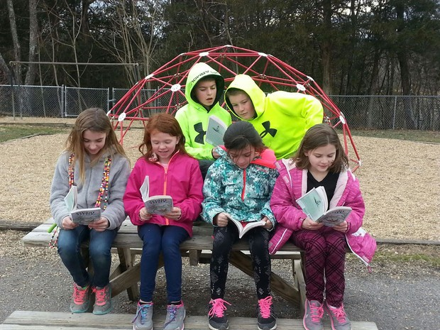 Picture of FRES students on the playground reading Stuart Little.