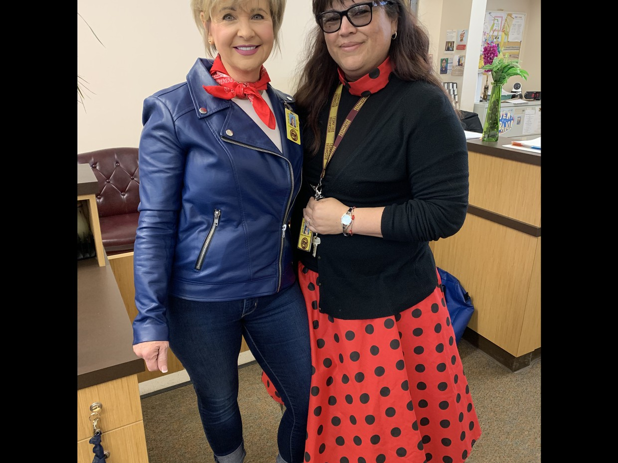 Dr. Barker and Mrs. Uriarte-Perez smile in their 50's garb.