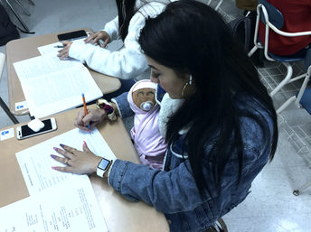 "a student cradles her ""baby"" for early childhood development class"
