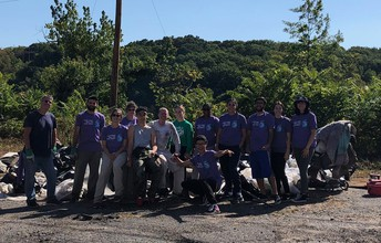 Group of HHS students and staff posing in front of the river clean up.