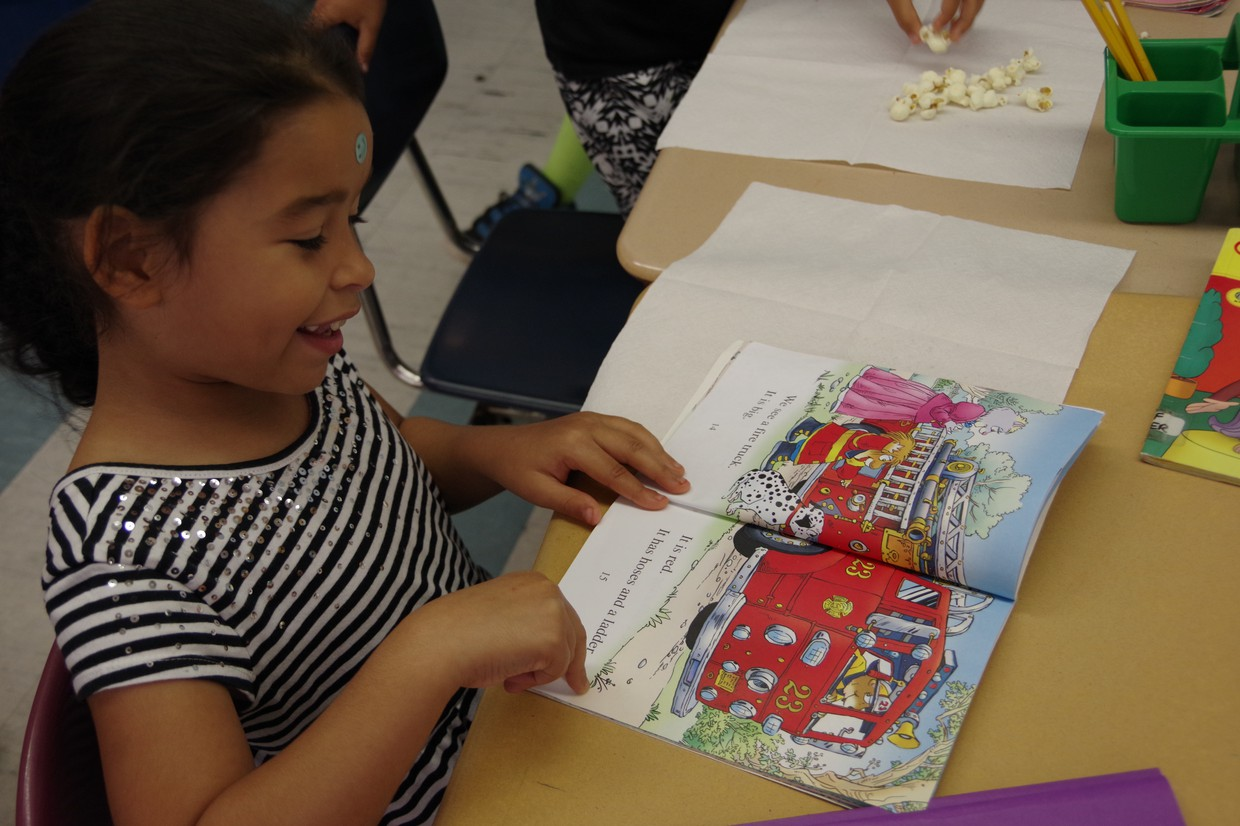 Elementary school young girl in striped shirt is reading a book with a red fire engine on the page.