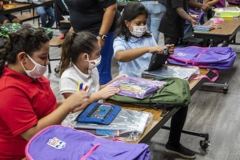 A group of students look through supplies in their newly donated backpacks