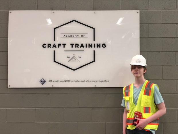 Picture of Tristan standing in front of the CRAFT Academy sign