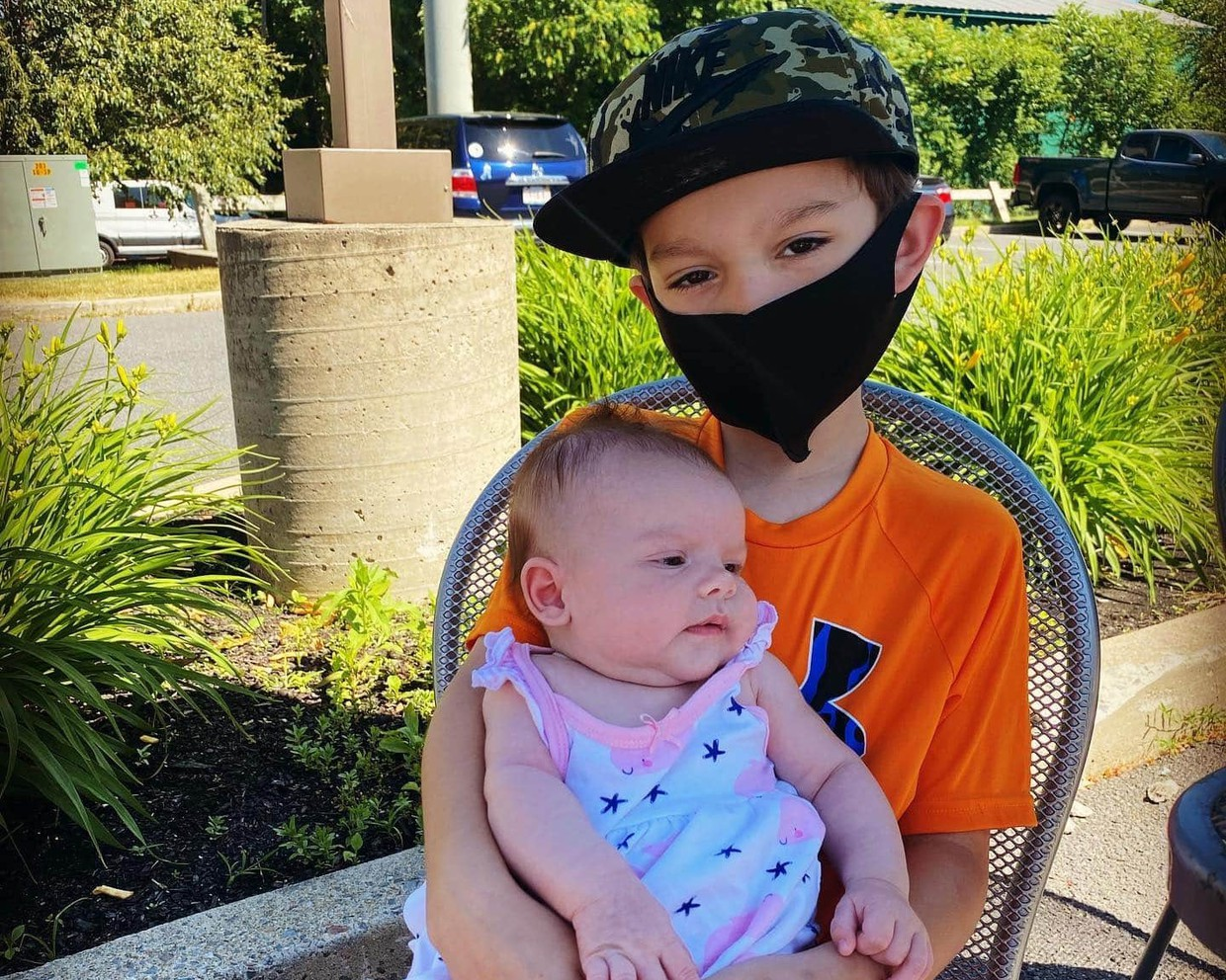 Student wearing a mask while out to lunch with his baby sister.