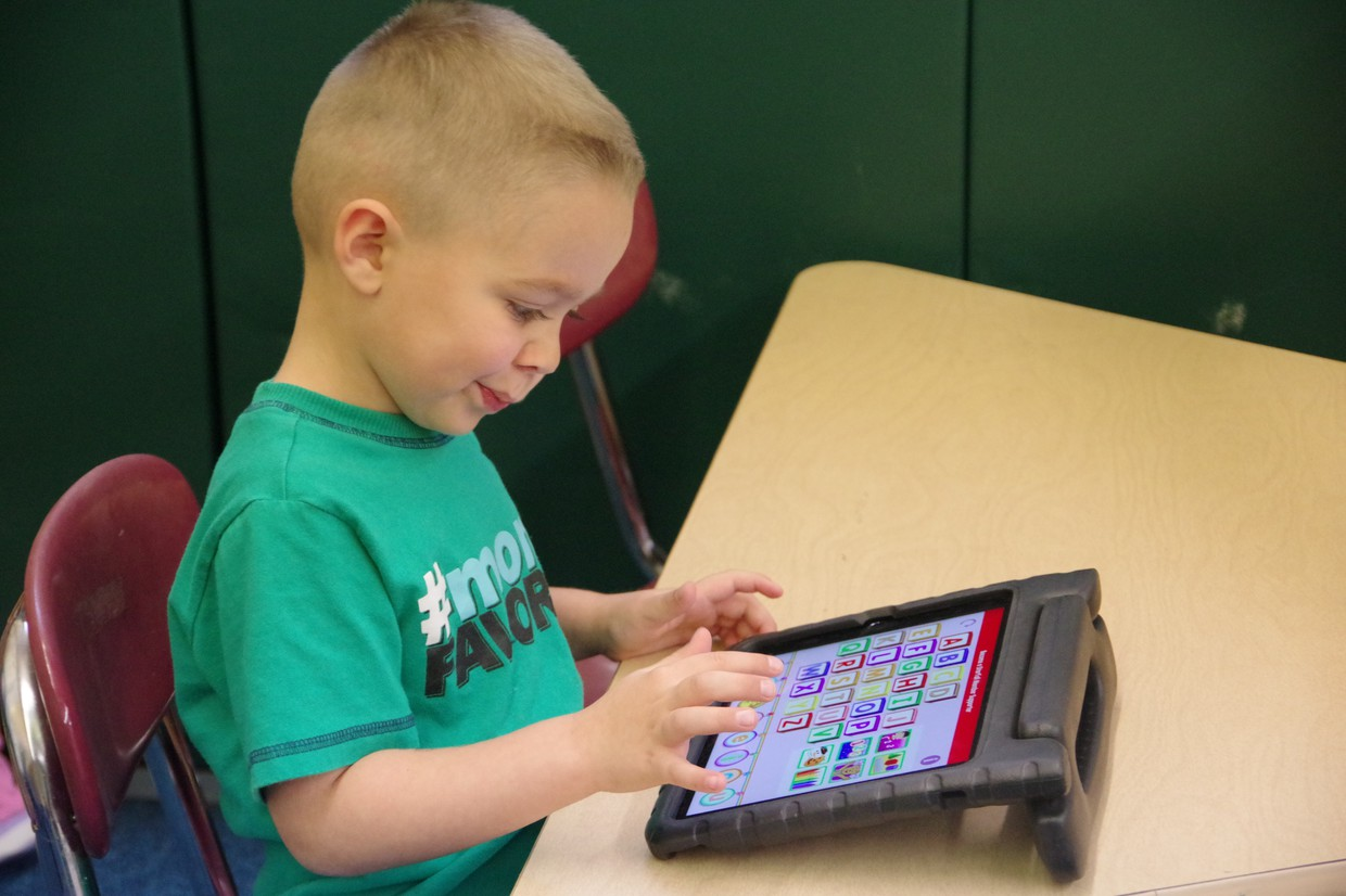 PreK student learning on a tablet.