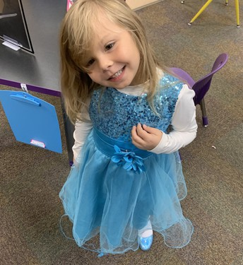Kindergarten student wearing a fancy, sparkly blue dress smiling widely