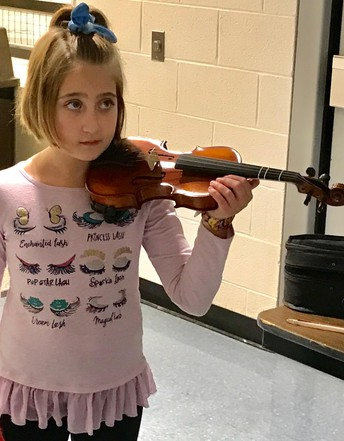 elementary students try out the strings