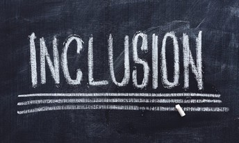 The word Inclusion written in caps on a chalkboard, underlined 3 times.