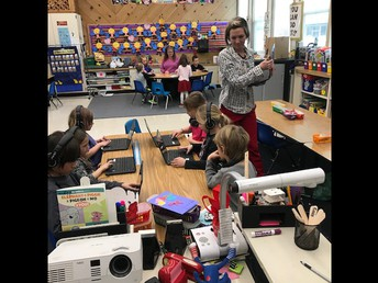Ms. Mary working with 1st graders using the laptops!
