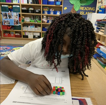 Student manipulates her colorful tiny blocks on her math paper