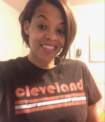 Lorrie smiles at the camera while wearing a brown shirt with Cleveland spelled out in orange letters.