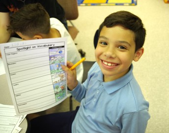 Male elementary student holding up his vocabulary work sheet.