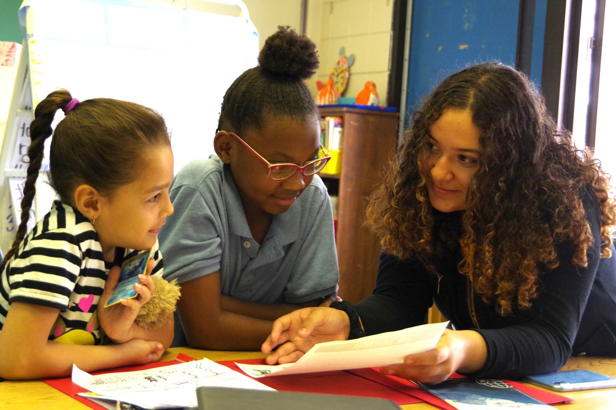 HHS North student mentoring two 2nd grade students at Kelly School.