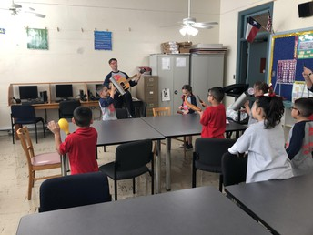 Father Clint stopped by 1st grade science to show the scholars how sound vibrates through music