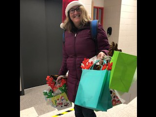 Mrs. Heide is loaded up with gifts and a smile