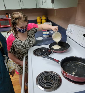 Student independently pouring pancake batter into a pan on the stove
