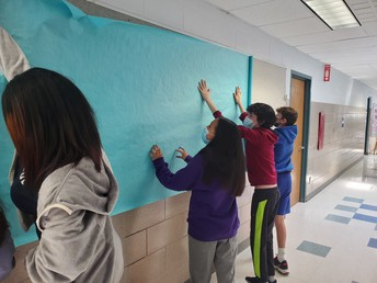 Students putting up bulletin boards for Advisory school service project