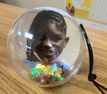 Student photo inside clear ornament ball with Christmas confetti
