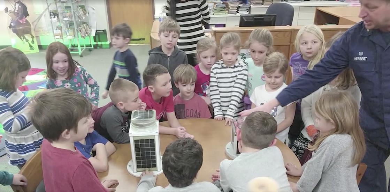 Many elementary children surround lighthouse lamp