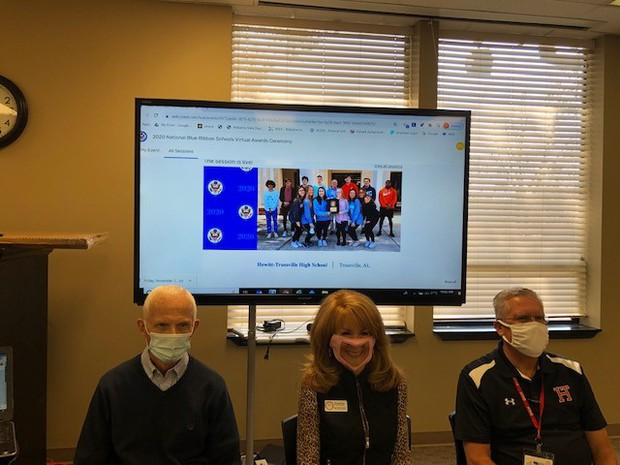 Picture with Dr. Ward, Dr. Neill and Mr. Salem sitting in front of virtual ceremony on screen