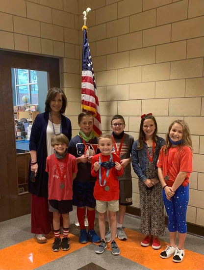 Principal with students standing in front of flag
