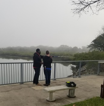 Student is being taught how to cast his line; fog is rolling in over the water
