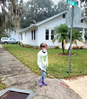 Arabella holding her can; she's approached an intersection and the sidewalk curves to the left