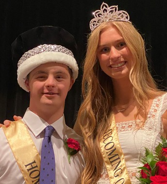 young man and woman wearing crowns and sashes