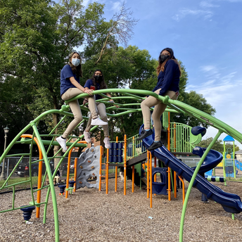 Three students sitting on top of the playground equipment.