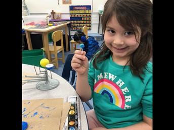 Painting a solar system model in Kindergarten.