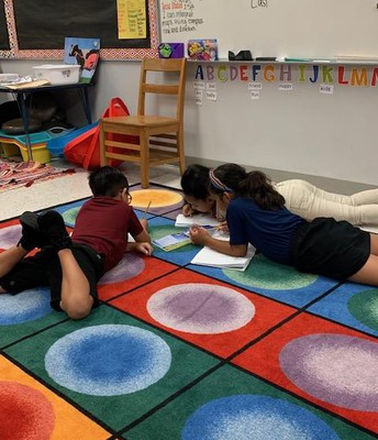 Students are working hard in groups to collaborate and work together.