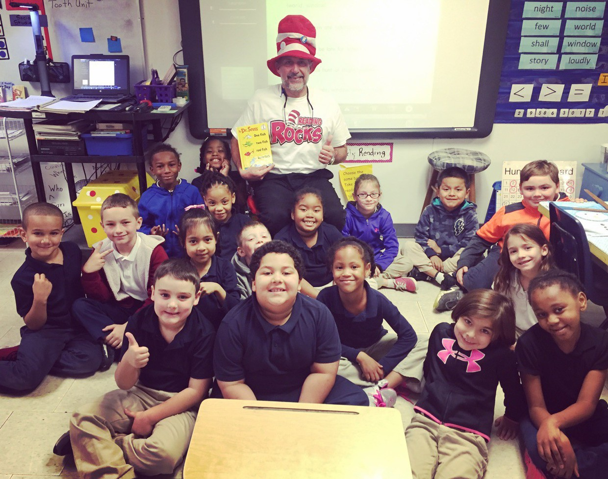 Mrs. Byrom's first-grade class celebrated Read Across America Week by inviting various guest readers to share their favorite Dr. Seuss books. Two of the classroom visitors were Mr. Limoges, principal, who read Green Eggs and Ham and Mr. Whaley, assistant principal, who read One Fish, Two Fish. Red Fish, Blue Fish.