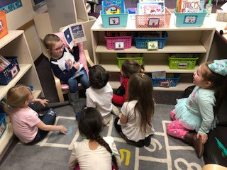 Kindergarten student reading to pre-schoolers