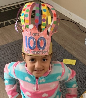 Jehieli smiling at the camera wearing constructed hat with words I am 100 days smarter