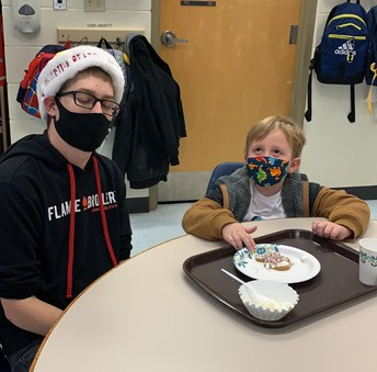 High school student Thomas assists Elementary student Kessler decorate a gingerbread man cookie