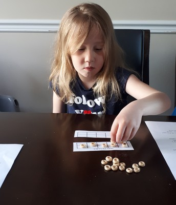 Rhea practicing her math with a 10 frame and cheerios