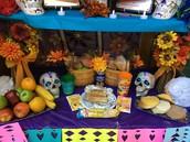 Pan de muertos, fruit, pan dulce, water & salt are on the third level.