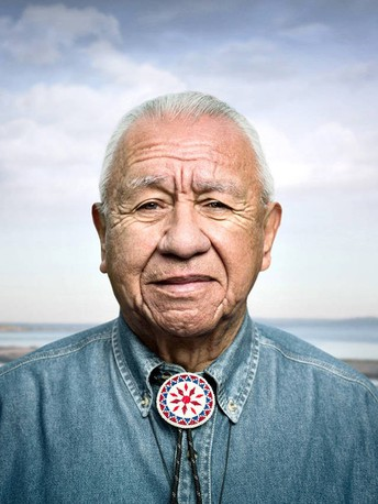 A high definition of older Billy Frank Jr. Wearing a denim shirt and tribal neck piece- very professional photo