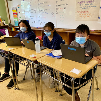 Three students working on laptops.