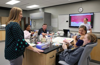 Instructor and students smiling and talking in science lab