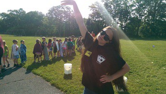A BHS ACES member standing with one arm in the air with a group of children behind her.