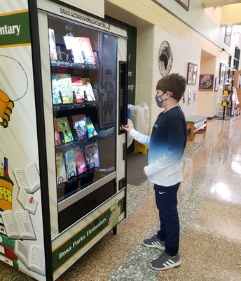 Student selecting books from the book vending machine