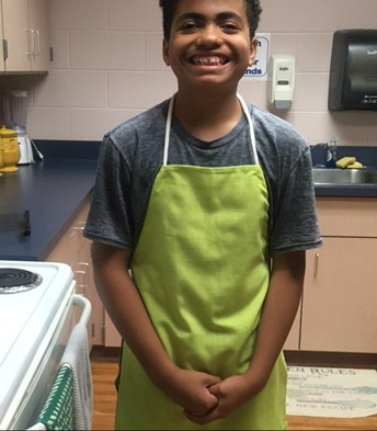 Addison smiling big while wearing lime green apron he just made
