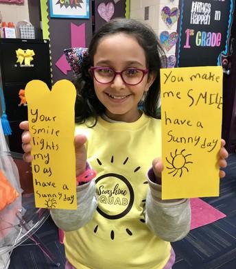 Student holding kindness bookmarks
