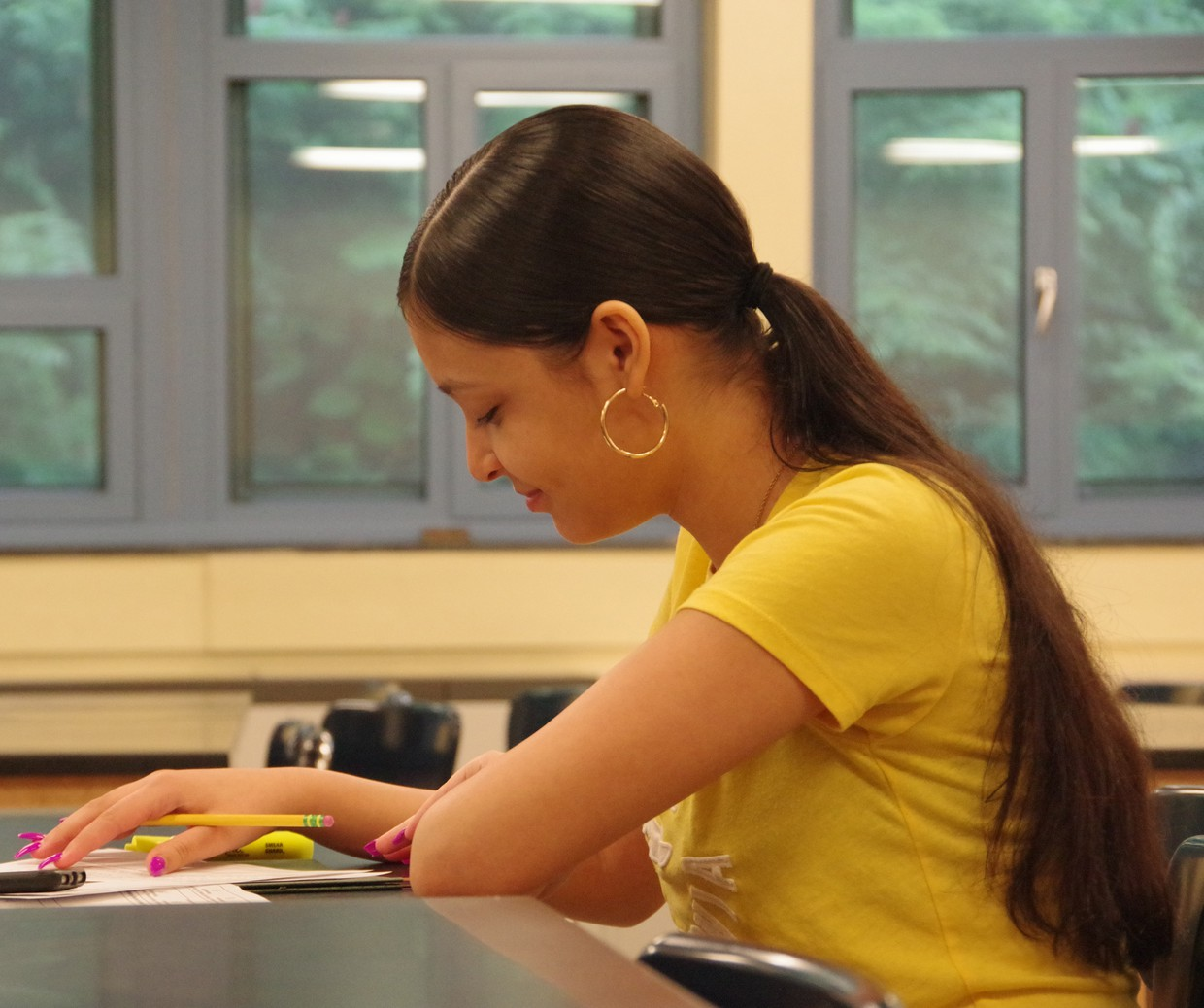 Female high school wearing a yellow shirt while seated at a desk holding a pencil