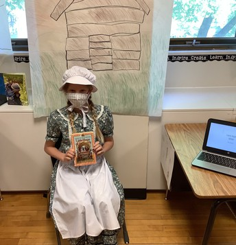 girl dressed in old dress for living wax museum presentation
