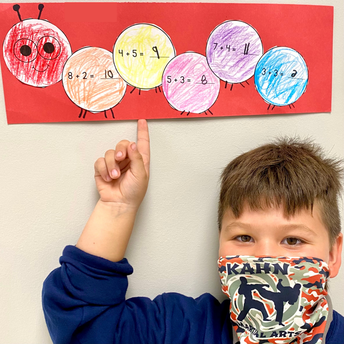 A student points to his artwork of a caterpillar with math equations on each body segment.