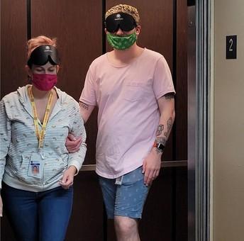A teacher guides a blindfolded teacher exiting an elevator