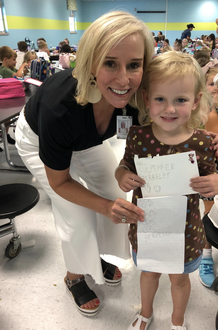 Mrs. Culpepper with student and note in the lunchroom.